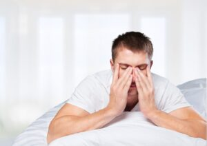 person pressing on their sinus's after a rough nights sleep